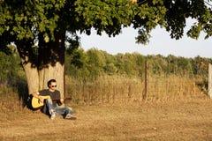 弹吉他的人在日落在槭树下 免版税库存图片