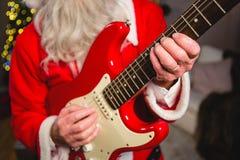 弹吉他的圣诞老人的中央部位 库存图片