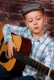 弹吉他的小男孩 免版税图库摄影