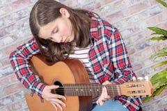 弹吉他的微笑的少年 免版税库存照片
