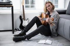 弹吉他的沉思音乐家,当坐地板时 免版税库存图片