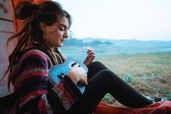 弹吉他的白种人妇女以后醒 图库摄影