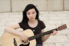 弹吉他的美丽的深色的女孩 免版税库存照片