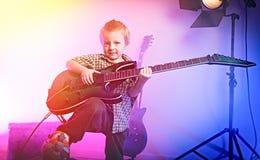 弹吉他,孩子吉他弹奏者的男孩 免版税图库摄影