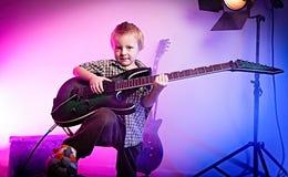弹吉他,孩子吉他弹奏者的男孩 免版税库存图片