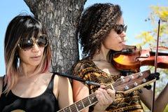 弹吉他和小提琴的妇女音乐家户外 免版税库存图片