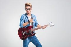 弹吉他在演播室和显示摇滚乐标志whi的花花公子 库存图片