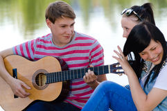 弹吉他的三个愉快的青少年的朋友在绿色夏天公园 库存照片