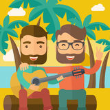 弹吉他的两个人在海滩 库存图片