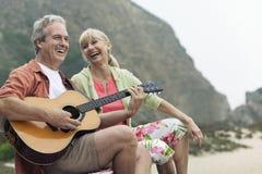 弹吉他的人由妇女在海滩 库存照片