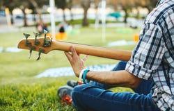 弹吉他的人的手坐草 免版税库存照片