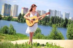 弹吉他的俏丽的女孩户外 图库摄影