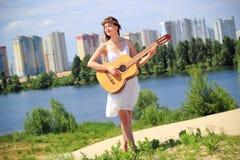 弹吉他的俏丽的女孩户外 免版税库存图片