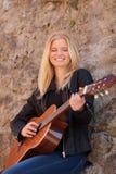 弹吉他的凉快的白肤金发的女孩室外 图库摄影