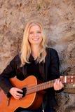 弹吉他的凉快的白肤金发的女孩室外 库存图片