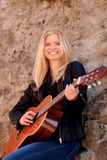 弹吉他的凉快的白肤金发的女孩室外 免版税图库摄影