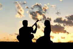 弹吉他的夫妇剪影在日落 免版税库存照片