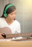 弹吉他的女孩和组成音乐 免版税库存图片