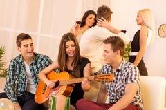 弹吉他的女孩在数日聚会 免版税库存照片