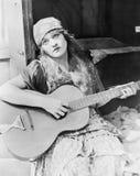 弹吉他的妇女画象 免版税库存照片