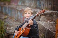 弹吉他的小男孩在秋天寒冷天 Children& x27; s intere 库存图片