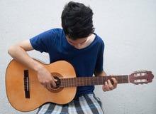 弹吉他的少年 图库摄影