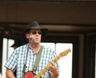 弹吉他的帽子的人在一个室外音乐会期间 免版税库存照片