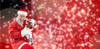 弹吉他的微笑的圣诞老人的综合图象,当跳舞时 免版税库存照片