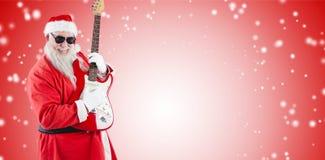 弹吉他的微笑的圣诞老人的综合图象 库存照片