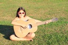 弹吉他的微笑的女孩 免版税库存图片