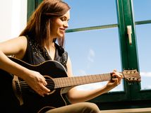 弹吉他的微笑的妇女由窗口 库存照片