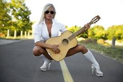 弹吉他的性感的妇女 免版税库存照片