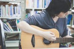 弹吉他的某些妇女在2017年6月18日的图书馆在曼谷TH 免版税库存图片