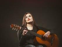 弹吉他的残疾女孩 免版税库存图片