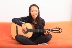 弹吉他的热带女孩 库存照片