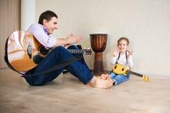 年轻弹吉他的父亲和小儿子 库存照片