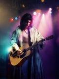 弹吉他的皮大衣的年轻岩石音乐家在音乐会 库存照片