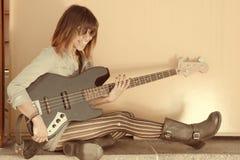 弹吉他的笑的妇女退色的画象 免版税库存照片