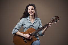 弹吉他的美丽的女孩 免版税库存图片
