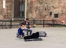 弹吉他的街道音乐家在入口对Castello Sforzesco 库存图片