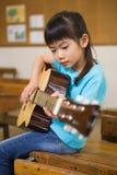 弹吉他的逗人喜爱的学生 免版税库存照片