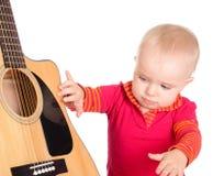弹吉他的逗人喜爱的矮小的小音乐家隔绝在白色backg 免版税库存图片