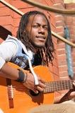 弹吉他的年轻黑人 免版税库存图片