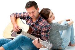 弹吉他的年轻夫妇 免版税库存图片