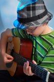 弹吉他的年轻男孩 免版税库存照片