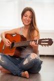 弹吉他的年轻美丽的妇女 免版税库存图片