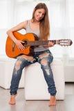 弹吉他的年轻美丽的妇女 免版税库存照片