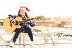 弹吉他,唱歌和微笑快乐由游泳池的年轻混合的族种女孩,与圣诞节圣诞老人帽子 免版税库存图片