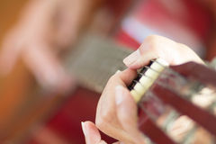 弹吉他,葡萄酒作用的妇女 库存照片