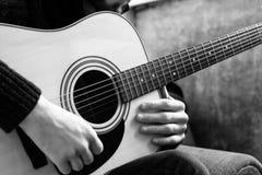 弹在一个混凝土墙的背景的年轻人一把声学吉他 免版税库存照片